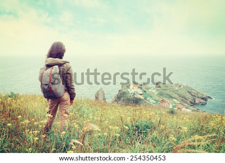 Traveler young woman standing on hill and looking to the town on peninsula. Image with instagram filter - stock photo