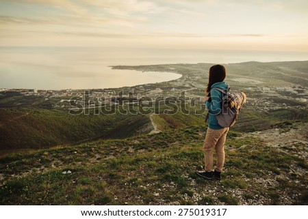 Traveler young woman with backpack standing on peak of mountain above the sea at sunset - stock photo