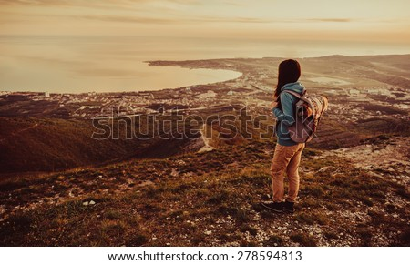 Traveler young woman with backpack standing on peak of mountain above the sea at sunset outdoor - stock photo