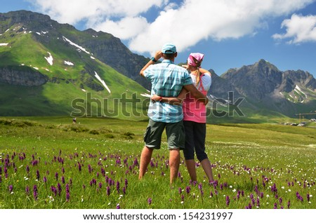 Travelers in an Alpine meadow. Melchsee-Frutt, Switzerland  - stock photo