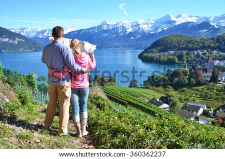 Travelers looking to the map. Switzerland - stock photo