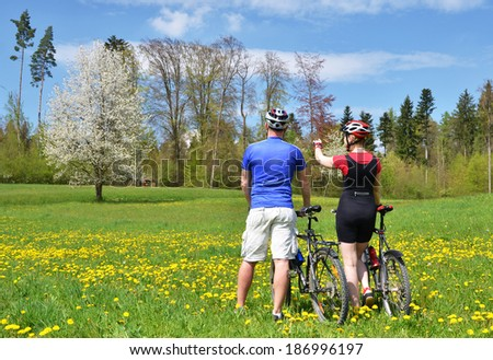 Travelers with mountain bikes in a meadow - stock photo