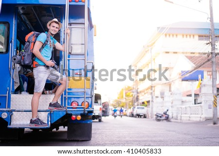 Traveling Asia. Young man with backpack enjoying trip on traditional thai bus. - stock photo