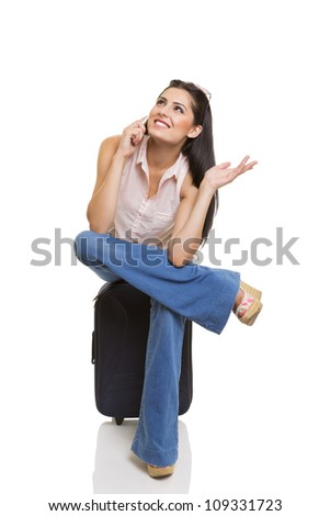 Traveling beautiful businesswoman waiting on vacation suitcase and having a cheerful phone conversation. Isolated on white background. - stock photo