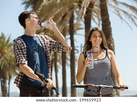 traveling by cycles couple drinking from plastic bottles of water and smiling - stock photo