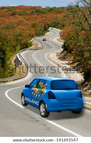 traveling car in flag of us state of oklahoma colors and beautiful road landscape for tourism and touristic adertising - stock photo