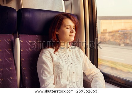 Traveling Comfort -Young woman sleeping feeling relaxed traveling  in the train. - stock photo