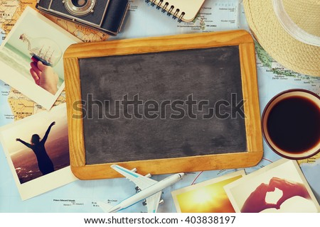 traveling concept. camera, cup of coffee, chalkboard and fedora hut. vintage filtered. top view  - stock photo
