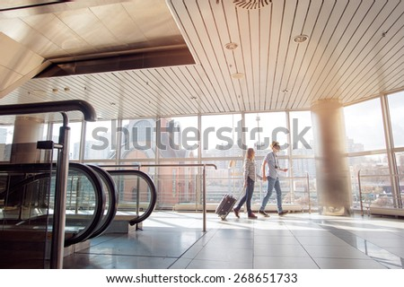 Traveling concept. Happy loving couple in casual wear walking with a luggage by airport terminal. - stock photo