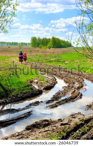Traveling cyclists at muddy country road - stock photo