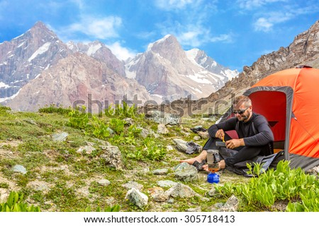 Traveling man eating meal. Hiker sitting in his orange camping tent and having lunch stove and cooking gear mountain landscape on background - stock photo