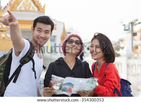 traveling man woman and senior tourist holding travel guide book in hand pointing to destination for visiting  - stock photo