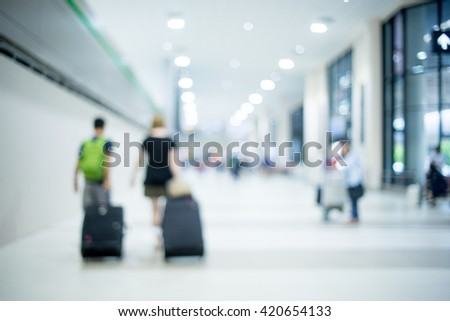 traveling people with trolley bags at the airport.Blurred background,Traveler at airport terminal blur background. - stock photo