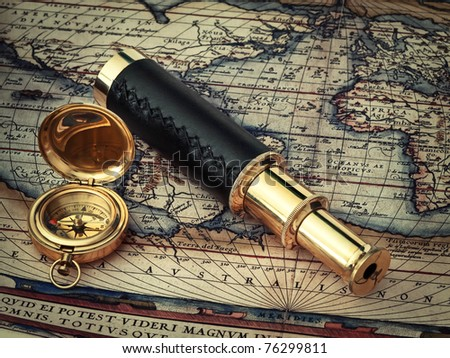 traveling theme: vintage telescope and compass at antique (17 century) map - stock photo