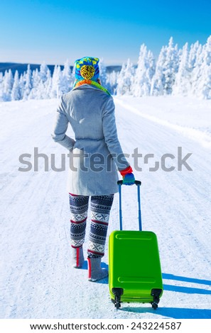 Traveling to Alps, back side of a young woman walking along snowy road with stylish green luggage,  winter vacation in Europe - stock photo