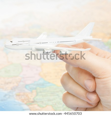 Traveling, tourism, communications and all things related - studio shot of a toy aircarft in hand and a world map on background - stock photo
