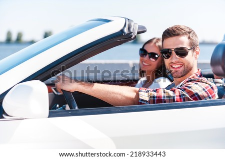 Traveling with comfort. Happy young couple enjoying road trip in their white convertible while both looking at camera and smiling - stock photo