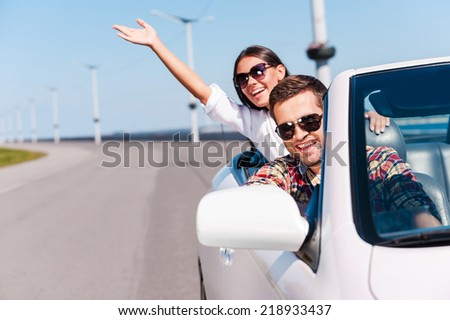 Traveling with fun. Happy young couple enjoying road trip in their white convertible  - stock photo