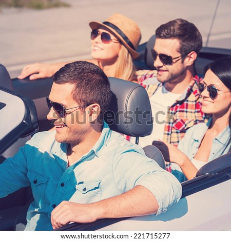 Traveling with fun. Top view of young happy people enjoying road trip in their white convertible - stock photo
