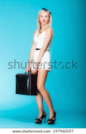 Traveling woman with luggage, sexy girl holding travel bag on vivid blue background - stock photo