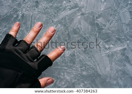 Traveller gloved hand touches the thin ice. - stock photo