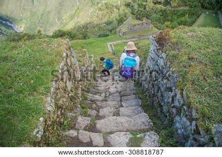Travellers walking on Winayhuayna, Inca ruins of agricultural center, The Inca Trail, Machu Picchu, Peru - stock photo