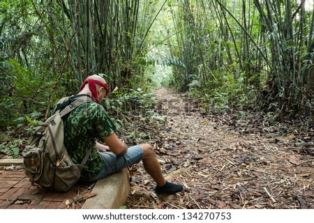 Travelling man sitting in the bamboo forest - stock photo