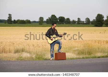 Travelling man with foot on suitcase on side of rural road playing his acoustic guitar while waiting for someone to stop and give him a ride. - stock photo