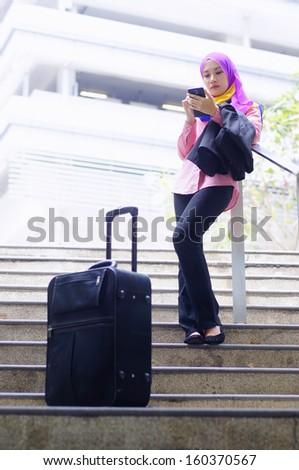 Travelling young businesswoman using tablet phone outdoor - stock photo