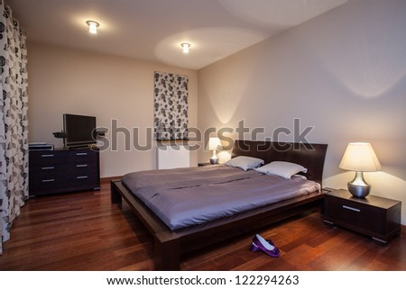 Travertine house - huge bed in a stylish bedroom - stock photo