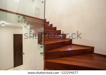 Travertine house - modern glass, metal and wooden staircase - stock photo