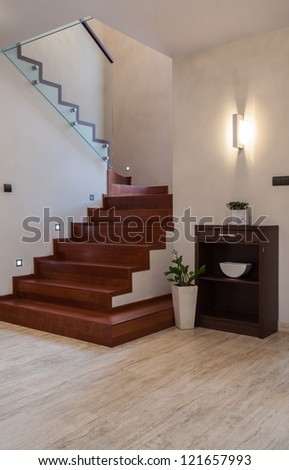 Travertine house: wooden steps and glass barrier - stock photo