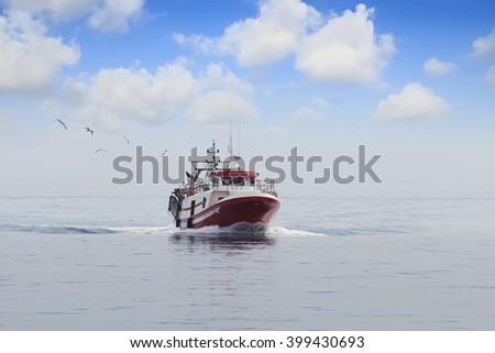 Trawler fishing boat sailing in open waters - stock photo