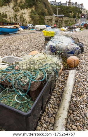 Trawler fishing nets and equipment set out on the stony beach at Beer, Devon, England, United Kingdom - stock photo