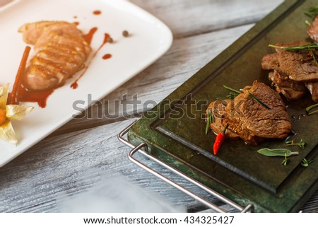 Tray and plate with meat. Pieces of cooked meat. Veal medallions and duck breast. Delicacies served at european restaurant. - stock photo