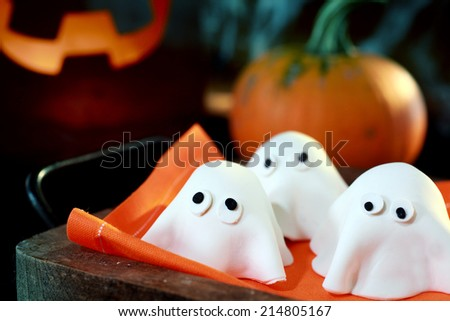 Tray of cute little Halloween monsters or ghosts made of pastry dough for a delicious party snack with a fresh pumpkin and glowing jack-o-lantern behind - stock photo