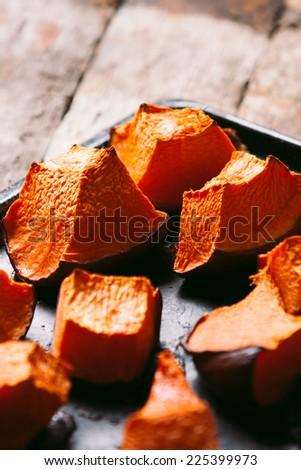Tray of freshly roasted pumpkin. Low key lighting. - stock photo