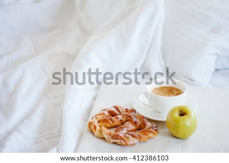 Tray with breakfast on a bed. Sweet pretzel, Cup of coffee and Apple - stock photo