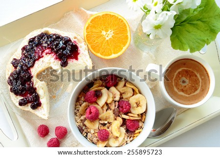 Tray with cereals with berries, roll with jam and sweet coffee - stock photo