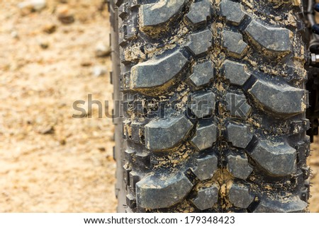 Tread tire coated in mud on an offroad - stock photo