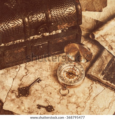treasure chest, compass and old map on wooden table - stock photo