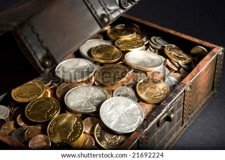 Treasure Chest filled with gold Krugerrand coins from  South Africa, silver Walking Liberty coins from the  United States of America and assorted change. - stock photo