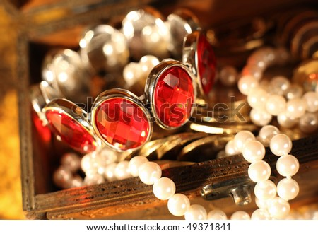 Treasure chest full of jewelry and pearl bracelet - stock photo