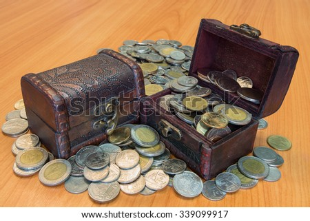 Treasure chest with countless coin and have a wood floor in the background - stock photo