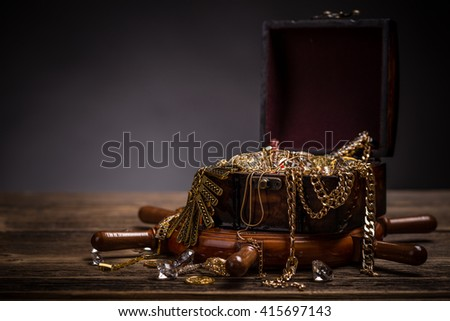 Treasure chest with jewellery on wooden background - stock photo