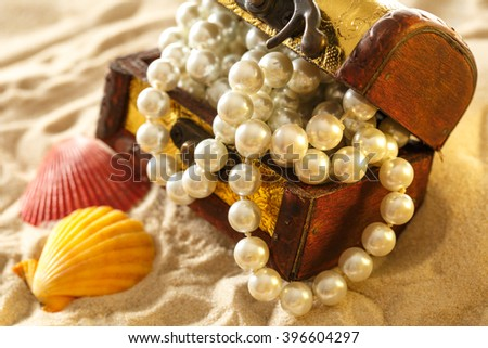 Treasure chest with seashells and pearl on sand - stock photo
