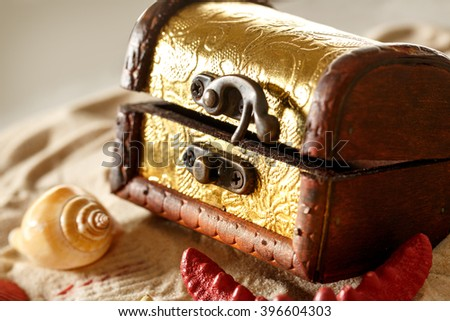 Treasure chest with seashells on sand background - stock photo