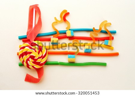 Treble clef and musical notes of candies isolated on white - stock photo