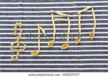 Treble clef and musical notes of pasta on striped background - stock photo