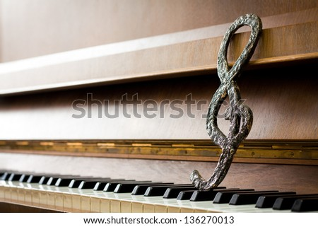 Treble clef on piano keys. Music concept. - stock photo